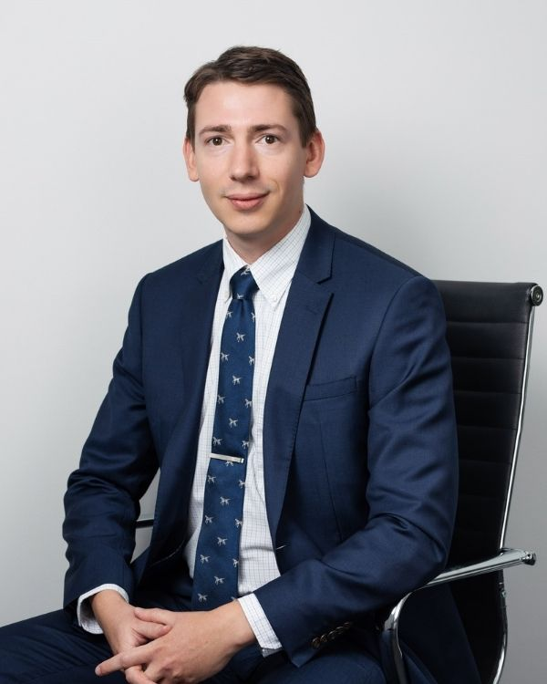 Keenan in a blue suit sitting in an office chair